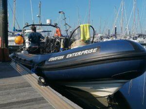 Blue RIB Starfish Enterprise tied up at a marina